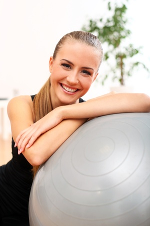 Close up of happy and beautiful woman with fitness ball at home photo