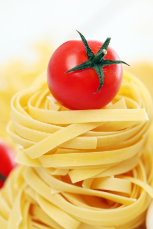 Italian pasta and cherry tomato isolated on white background photo