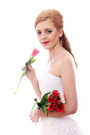 Portrait of young bride smelling red rose photo