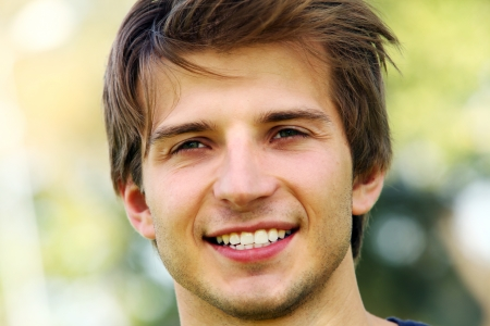 handsome boy: Portrait of young and smiling cute man in park Stock Photo