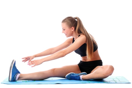 Happy girl doing fitness exercises on a mat over white background