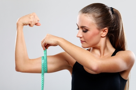 bicep: Beautiful fitness girl measure her biceps with a ruler over grey background
