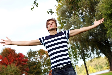 Portrait of happy and attractive young man at warm day in autumn park photo