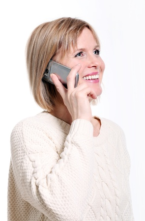 Caucasian middle aged woman on cellphone smiling over white background photo