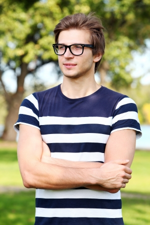 man with glasses: Portrait of young and smiling cute man with glasses in park