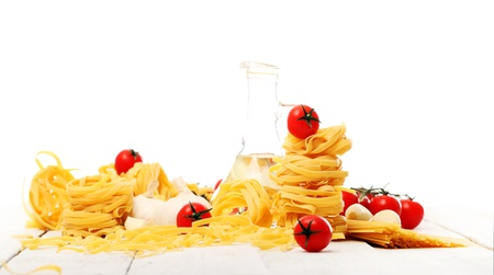 Italian pasta, cherry tomato and bottle of water on wooden surface isolated on a white background photo