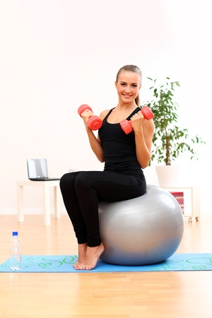 Happy and young woman working out with dumbbells on fitness ball at home photo