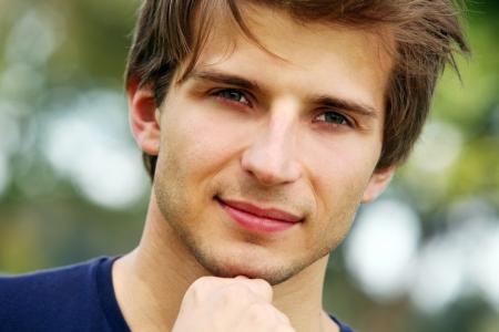 beau jeune homme: Portrait d'un homme jeune et mignonne souriante dans le parc