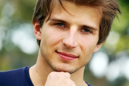 handsome young man: Portrait of young and smiling cute man in park Stock Photo