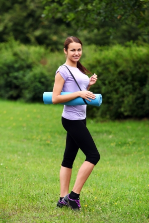 Portrait of young and beautiful girl with fitness mat in the park photo