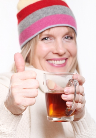 atcamera: Mid age Woman With Hot tea Wearing Winter Clothes showing thumbs up on a white background
