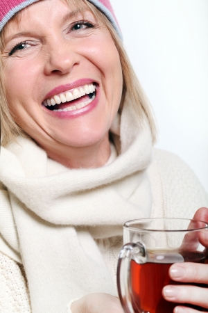 atcamera: Mid age Woman With Hot tea Wearing Winter Clothes on a white background Stock Photo