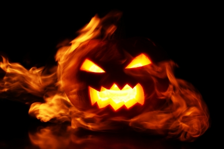 halloween pumpkin in fire over a black background photo