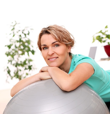 one mid adult woman: Cute and smiling middle aged woman with abs ball at home