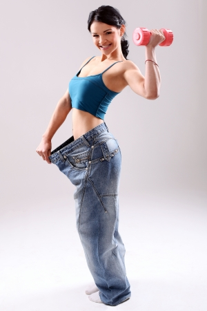 Cute and slim girl with dumbbell wearing old jeans after weight loss photo