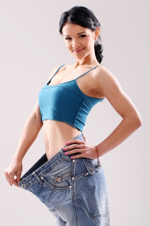 Cute slim girl wearing old jeans after weight loss, in studio