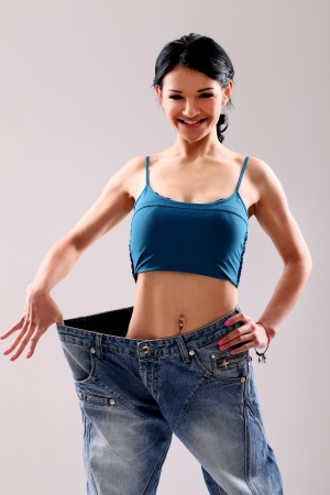 Cute slim girl wearing old jeans after weight loss in studio photo