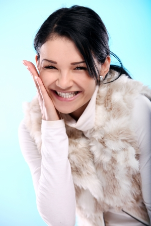 Beautifull smiling young girl in fur isolated on a blue Banco de Imagens