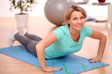slim mid aged woman do her fitness exercises at home photo