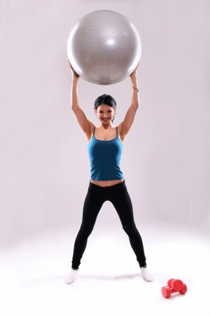 Cute and young fitness girl with abs ball in studio photo