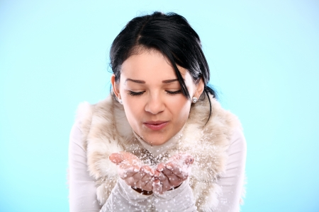 Cute and attractive girl blowing on christmas snow isolated on a blue photo