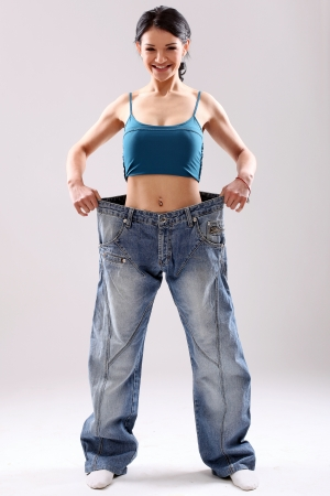 Cute slim girl wearing old jeans after weight loss, in studio photo