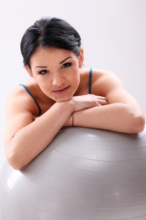 Cute young fitness girl with abs ball in studio photo