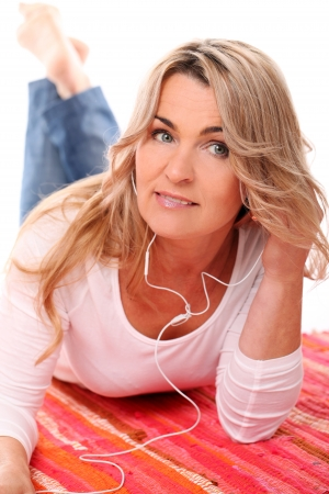 Beautiful Mid aged woman listening music with headphones photo