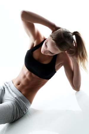 sporty and attractive woman do fitness exercise isolated on a white photo