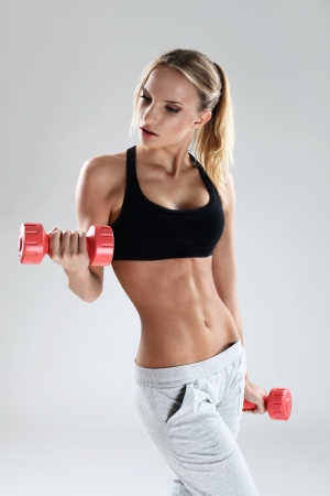 sporty and attractive woman do exercise with red dumbbells photo