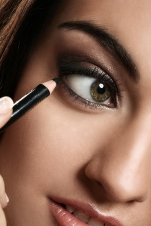 eye liner: Beautiful woman using eye pencil portrait isolated on a brown