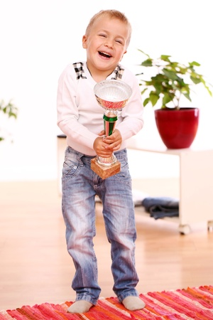 Happy boy with gold cup on a mat at home photo