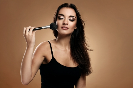 Beautiful woman use a brush on her face isolated on a brown photo