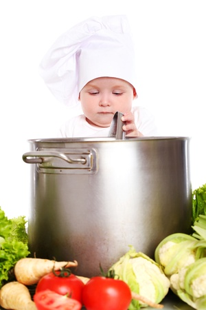 pots pans: Baby cook looking in pan and vegetables around isolated on a white