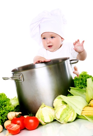 Baby cook with pan and vegetables isolated on a white photo