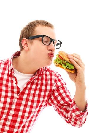 comiendo pan: Hombre divertido en vidrios come la hamburguesa aislado en un blanco