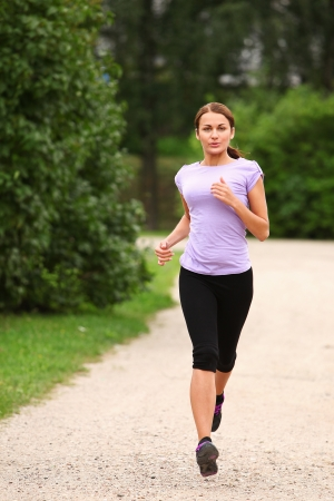 Young and attractive sporty girl running in the park photo