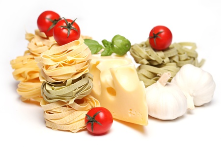 Dry pasta, cherry tomatoes, garlic, cheese and basil photo over a white background photo