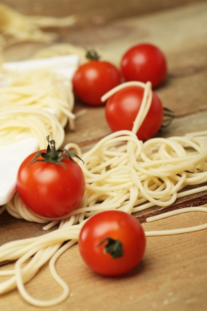 Closeup of fresh tomatoes with spaghetti on a plate over wooden surface photo