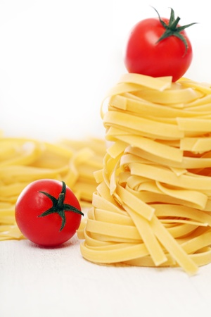 Dry pasta and cherry tomatoes composition over a white background photo