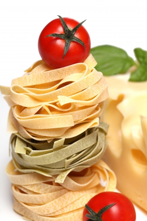 Dry pasta, cherry tomatoes, cheese and basil photo over a white background photo