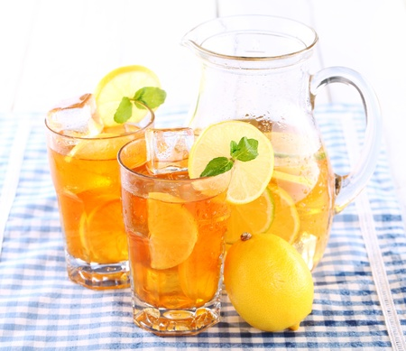 pitcher: Close up of fresh and cold ice tea with sliced lemon and mint