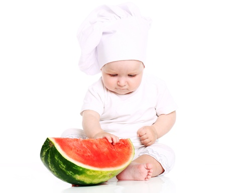 Happy baby cook eating watermelon isolated on a white photo