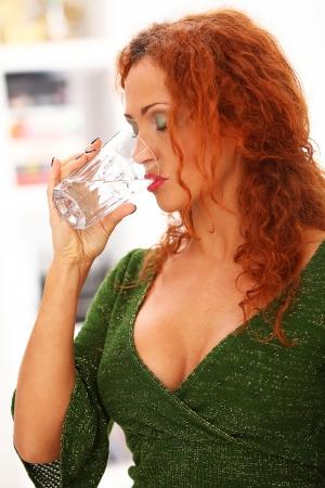 Beautiful redhead woman drinking water at home photo