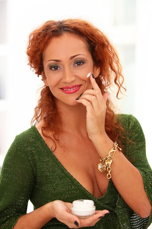 Beautiful redhead woman applying cream on a face in studio photo