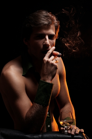 Artistic picture of handsome man with naked torso smoking cigar and drinking wine Stock Photo - 16821512