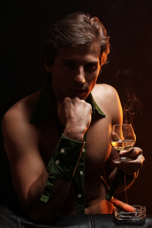 Artistic picture of handsome man with naked torso smoking cigar and drinking wine Stock Photo - 16821515