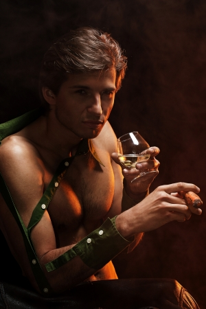 Artistic picture of handsome man with naked torso smoking cigar and drinking wine Stock Photo - 16821518