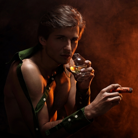Artistic picture of handsome man with naked torso smoking cigar and drinking wine Stock Photo - 16821459