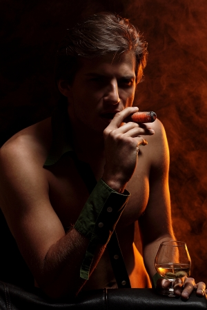 Artistic picture of handsome man with naked torso smoking cigar and drinking wine Stock Photo - 16821524